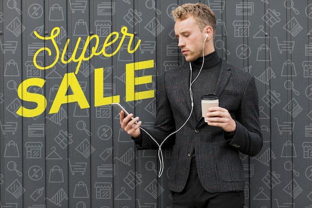 若い男が一杯のコーヒーを保持していると携帯電話を見て 無料 Psd