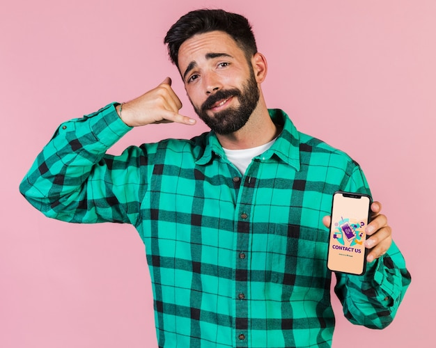 Young man pretending speaking at phone and holding a cell phone mock up Free Psd