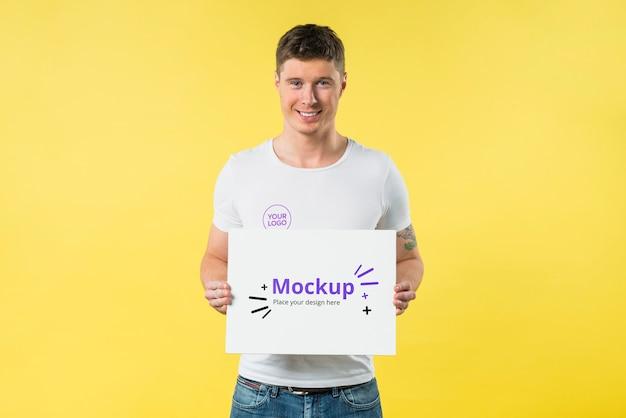 Молодой человек, стоящий и держащий макет спереди Бесплатные Psd