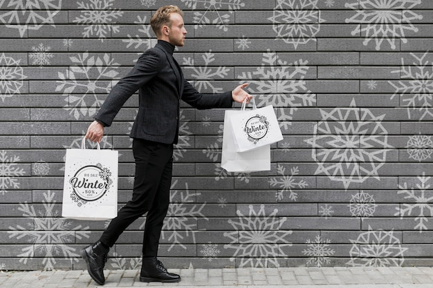 Young man walking with shopping bags Free Psd