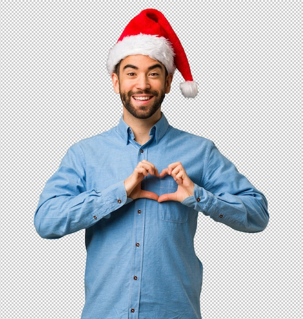 3345722847970 Young man wearing santa hat doing a heart shape with hands PSD file ...