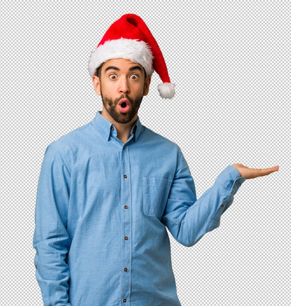 6d8112f7dccdc Young man wearing santa hat holding something on palm hand PSD file ...