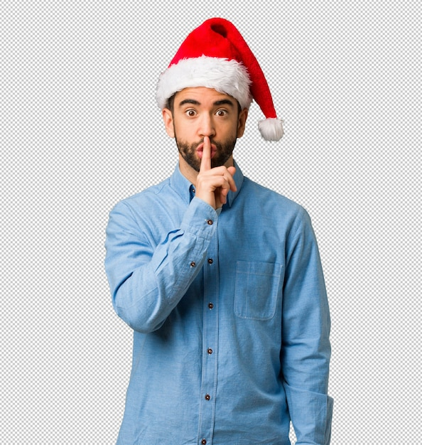 Young man wearing santa hat keeping a secret or asking for silence Premium Psd
