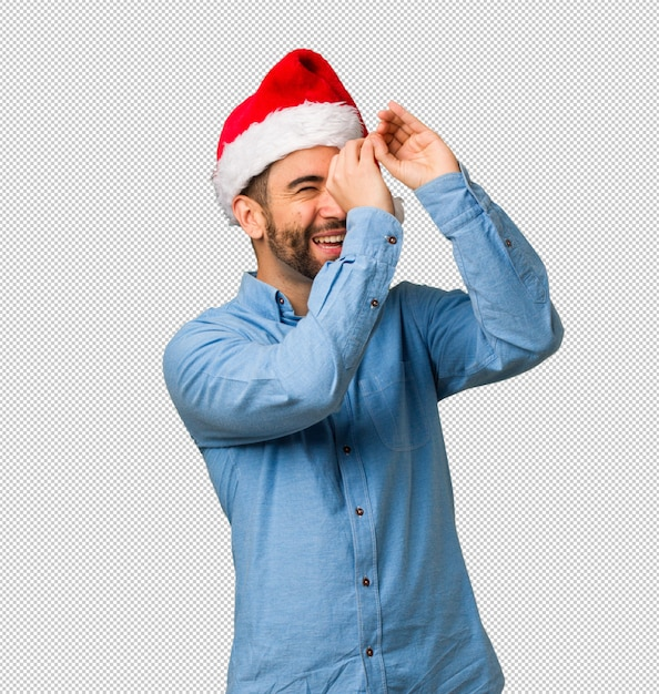 Young man wearing santa hat making the gesture of a spyglass Premium Psd
