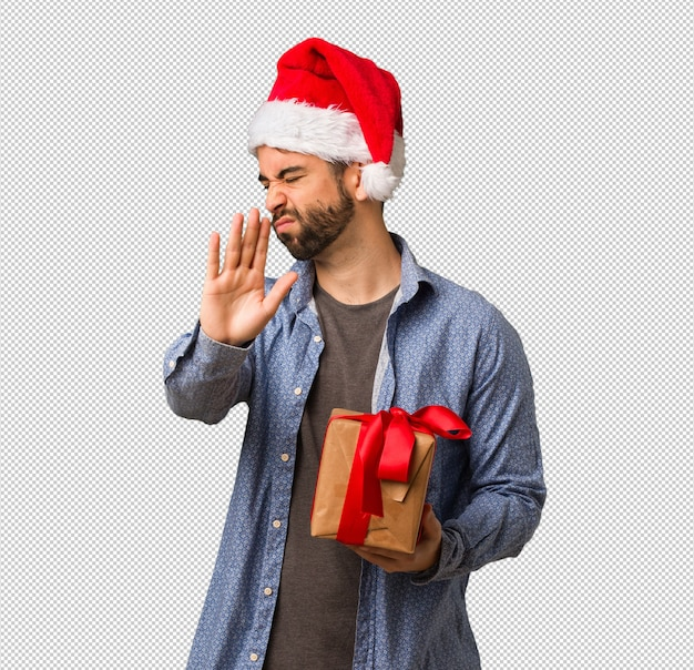 e13b01165d097 Young man wearing santa hat putting hand in front Premium Psd