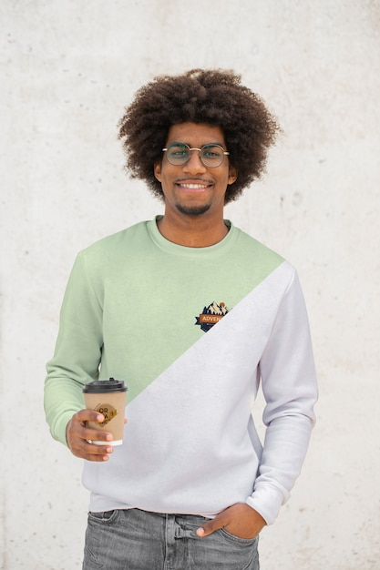 Young man with hoodie drinking coffee Free Psd