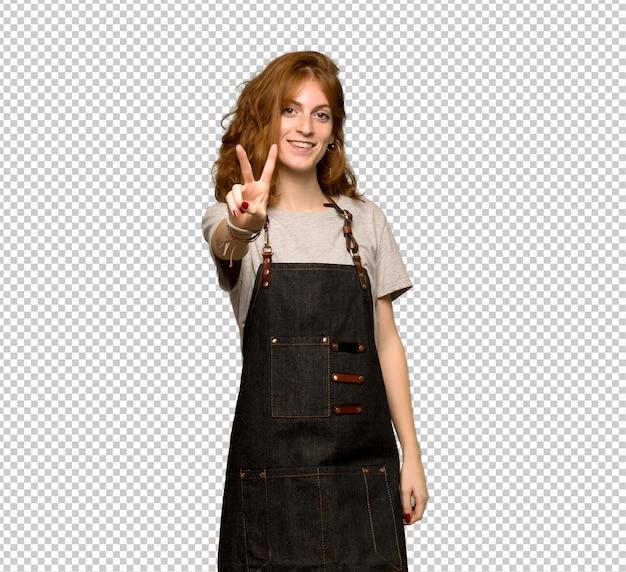 Рыжая молодая женщина с фартук улыбается и показывает знак победы Premium Psd