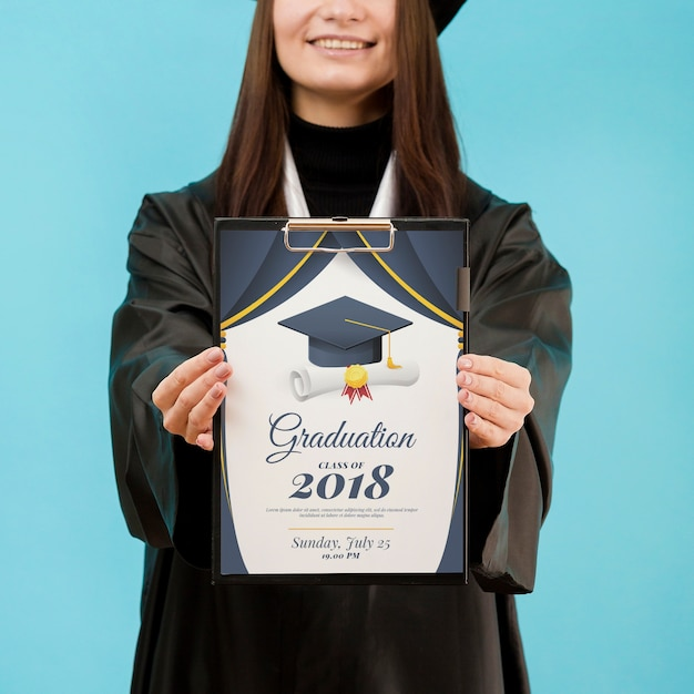 Young student holding diploma with mock-up Free Psd