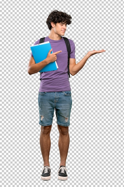 Young student man holding copyspace imaginary on the palm to insert an ad Premium Psd