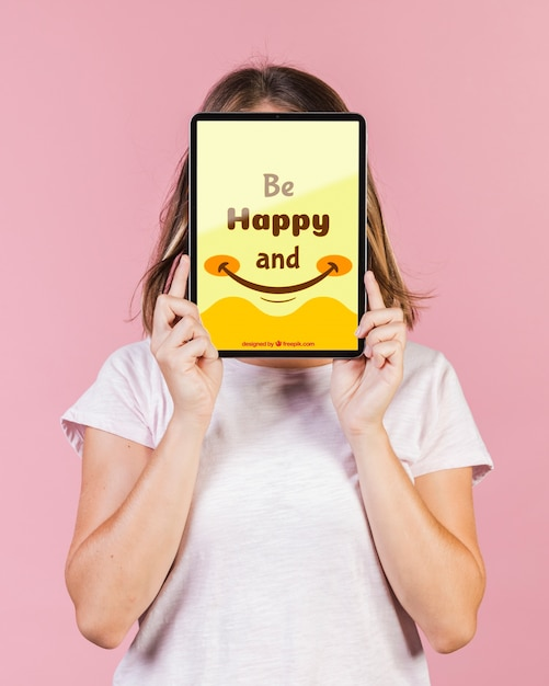 Young woman covering the face with a tablet mock-up Free Psd