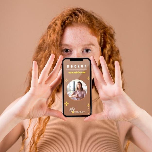 Молодая женщина, держащая макет смартфона Бесплатные Psd