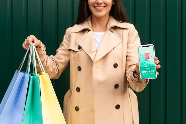 Young woman holding shopping bags and a phone mock-up Free Psd