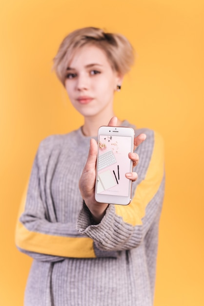 Young woman holding smartphone mockup Free Psd