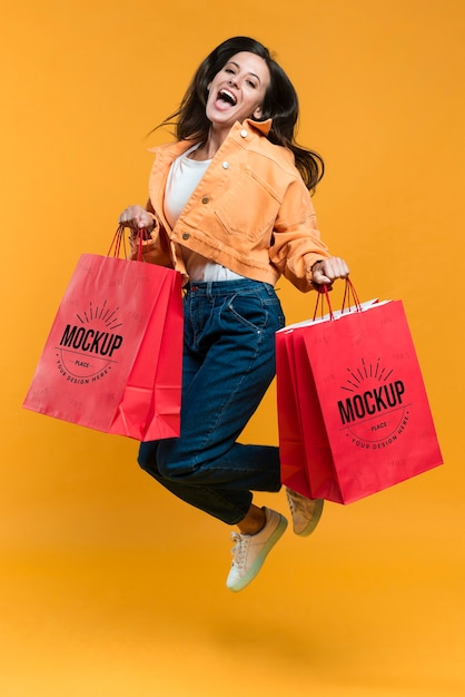 Young woman jumping and holding shopping bags mock-up Free Psd