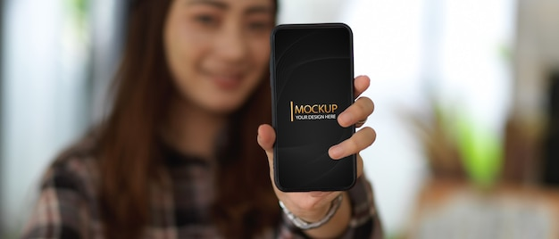Young woman showing mockup smartphone with blurred background Premium Psd