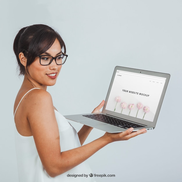 Young woman with laptop's mock up Free Psd