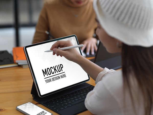 Young woman working on mockup screen tablet in comfortable workspace Premium Psd
