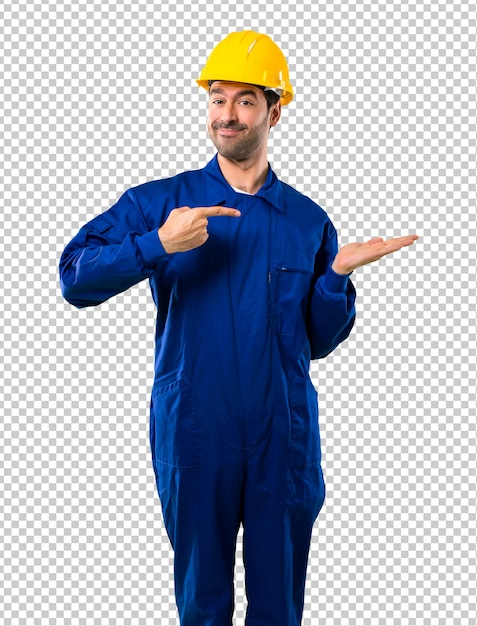 Young workman with helmet holding copyspace imaginary on the palm to insert an ad Premium Psd