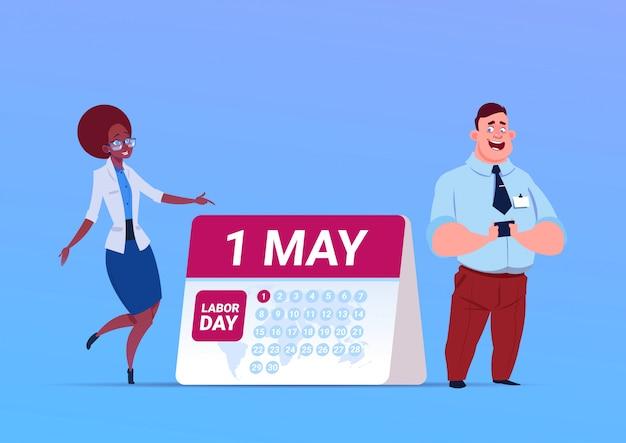 Счастливый 1 мая день труда плакат с мужчиной и женщиной по календарю Premium векторы