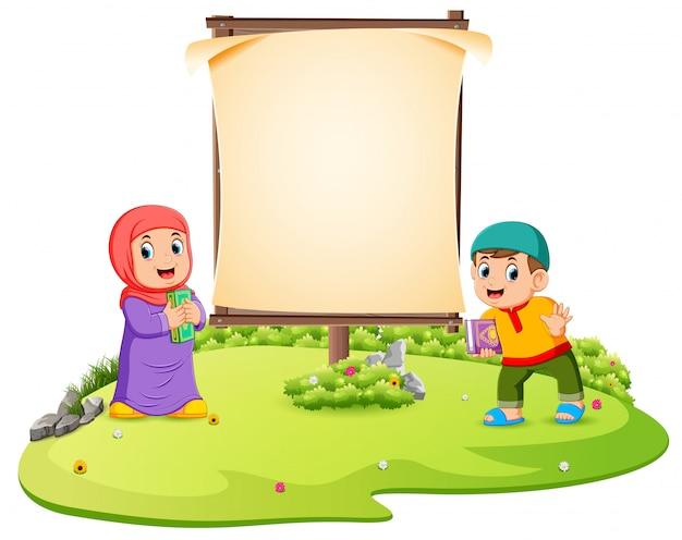 2人の子供が空白の枠の近くの緑豊かな庭園に立っています。 Premiumベクター