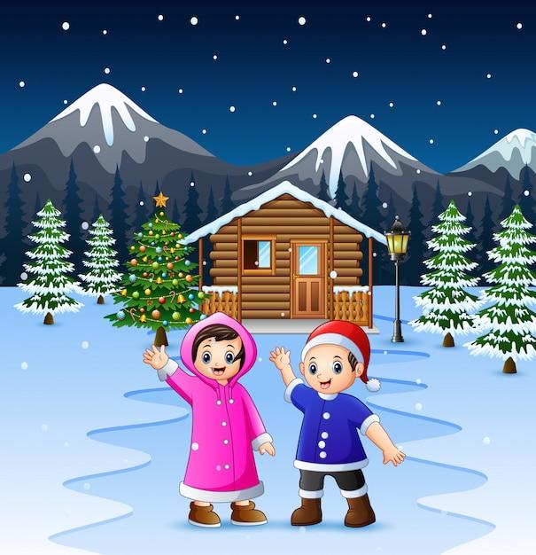 雪の木製家の前で手を振る2人の子供 Premiumベクター