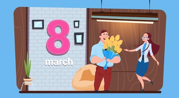 幸せな女性の日3月8日休日を持つ男持株花束挨拶女の子 Premiumベクター