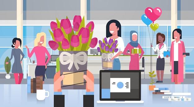 幸せな3月8日の休日の概念のオフィスで女性のグループに花をあげるビジネスマンの手 Premiumベクター