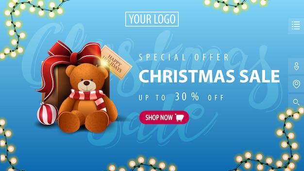 特別オファー、クリスマスセール、最大30%オフ、ピンクのボタン、ガーランド、テディベア付きのプレゼントを備えたミニマルなスタイルの青い割引バナー Premiumベクター