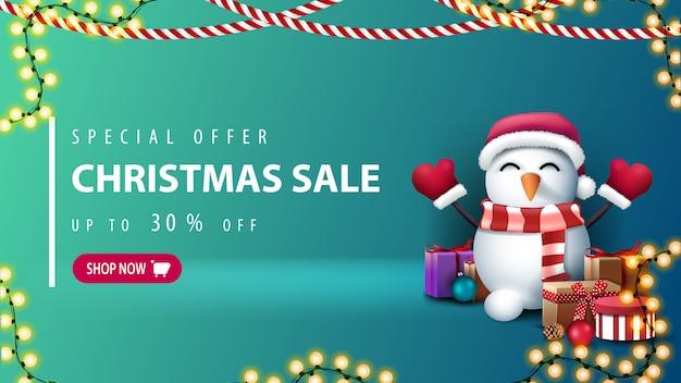 Специальное предложение, рождественская распродажа, скидка до 30%, зеленый баннер со скидкой с розовой кнопкой, гирляндами и снеговиком в шапке санта-клауса с подарками Premium векторы