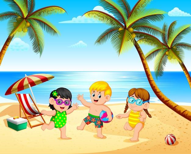 青い空の下でビーチで遊ぶ3人の子供たちとの美しい景色 Premiumベクター