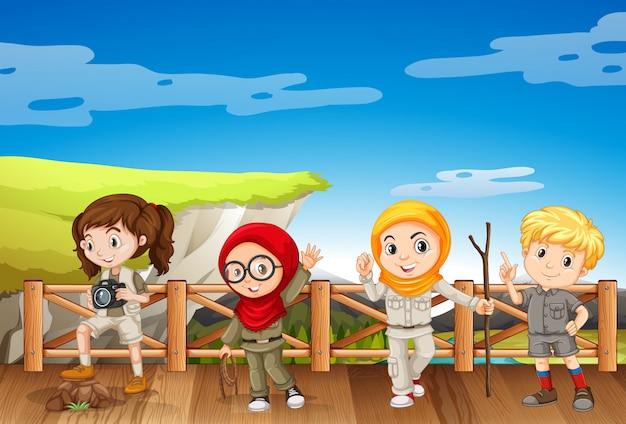 山でサファリの衣装で4人の子供 無料ベクター