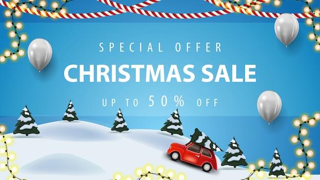 Специальное предложение, новогодняя распродажа, скидка до 50%, синий баннер со скидкой с белыми воздушными шарами, гирляндами и мультяшным зимним пейзажем с красным винтажным автомобилем с рождественской елкой Premium векторы