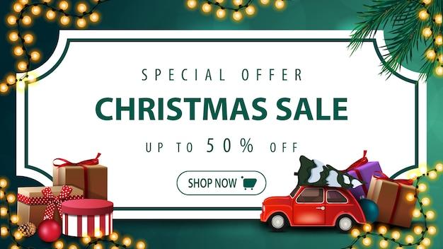 特別オファー、クリスマスセール、最大50%オフ、ビンテージチケット、クリスマスツリーの枝、花輪、クリスマスツリーを運ぶ赤いヴィンテージ車の形のホワイトペーパーシートと緑の割引バナー Premiumベクター