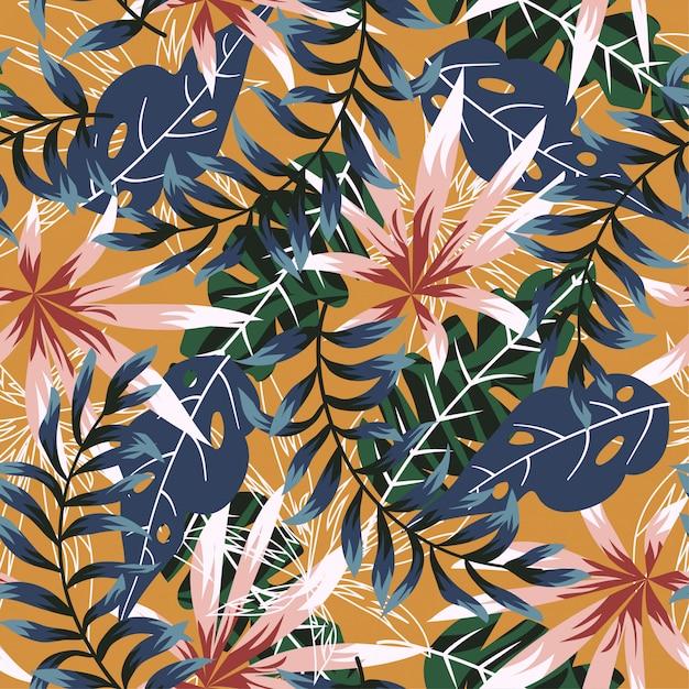 カラフルな熱帯の葉とオレンジ色の背景の植物のトレンドのシームレスパターン Premiumベクター