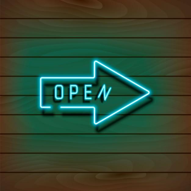 木製の壁に開いているネオンブルーの矢印 Premiumベクター