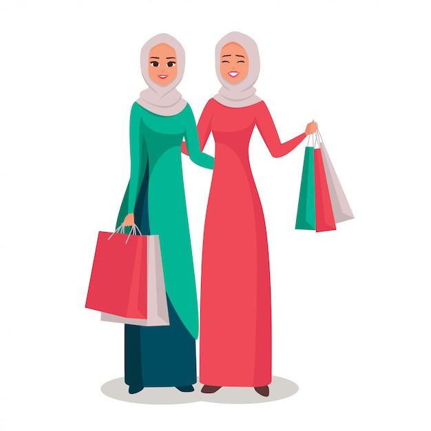 買い物袋とヒジャーブのイスラム教徒の女性の笑顔 Premiumベクター