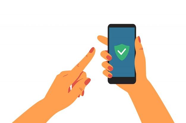 画面に緑色の盾を持つ携帯電話を持っている人間の手。 Premiumベクター