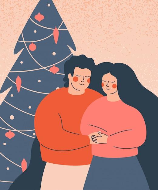 Счастливые люди отмечают зимние каникулы. молодая семья стоит у украшенной елки. Premium векторы