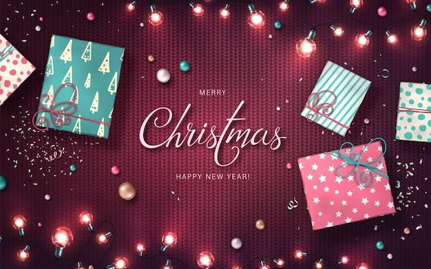 Рождественский фон с рождественские огни, безделушки, подарочные коробки и конфетти. праздничные светящиеся гирлянды из светодиодных лампочек на трикотажной фактуре. украшения из реалистичных разноцветных светильников для новогодних открыток Premium векторы