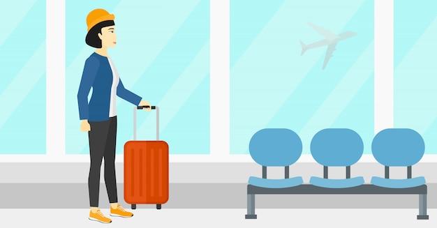 Женщина в аэропорту с чемоданом Premium векторы