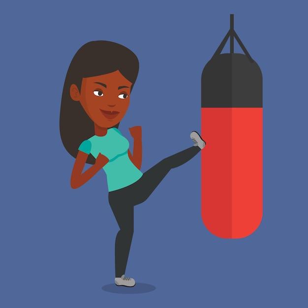 パンチングバッグと運動の女性。 Premiumベクター