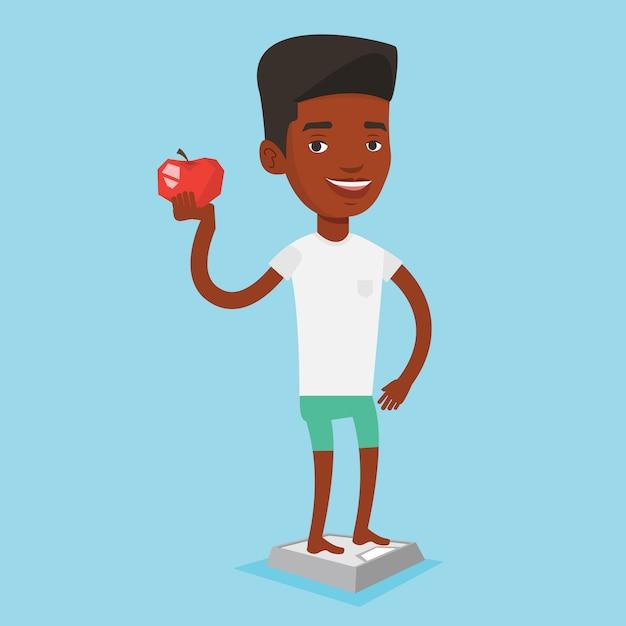 スケールの上に立って、手にリンゴを保持している男。 Premiumベクター