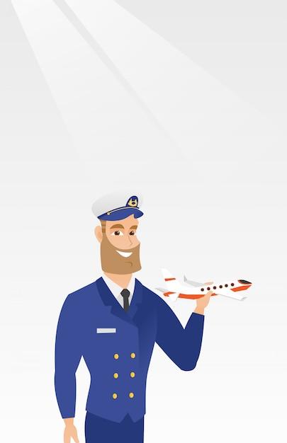 飛行機のモデルと陽気な航空会社のパイロット。 Premiumベクター