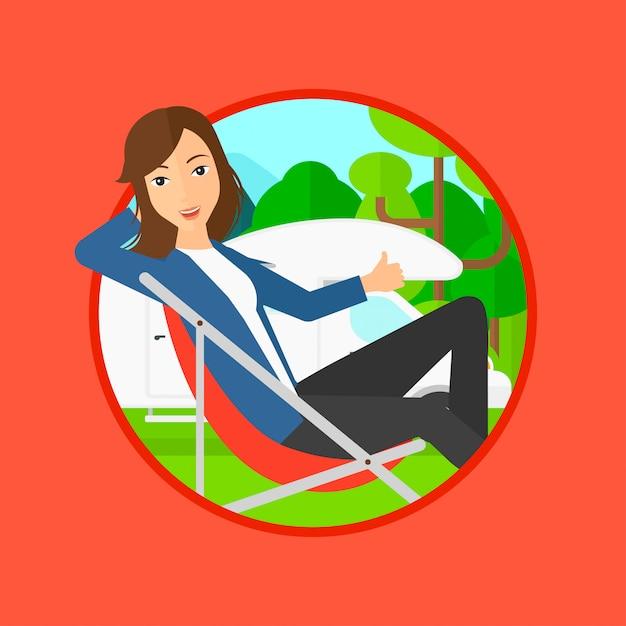 キャンピングカーの前の椅子に座っている女性。 Premiumベクター