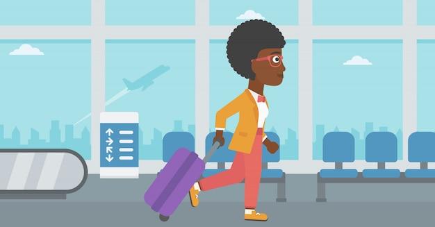 空港でスーツケースを持って歩く女性。 Premiumベクター
