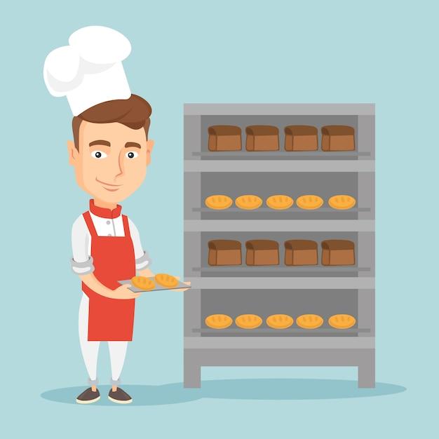 Счастливый молодой мужской пекарь держит поднос хлеба. Premium векторы
