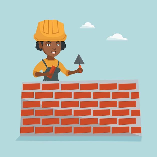 若いアフリカ職人がレンガの壁を構築します。 Premiumベクター