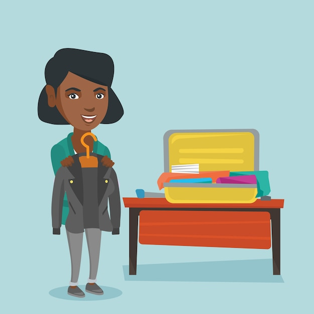 アフリカの女性がスーツケースに服を梱包します。 Premiumベクター