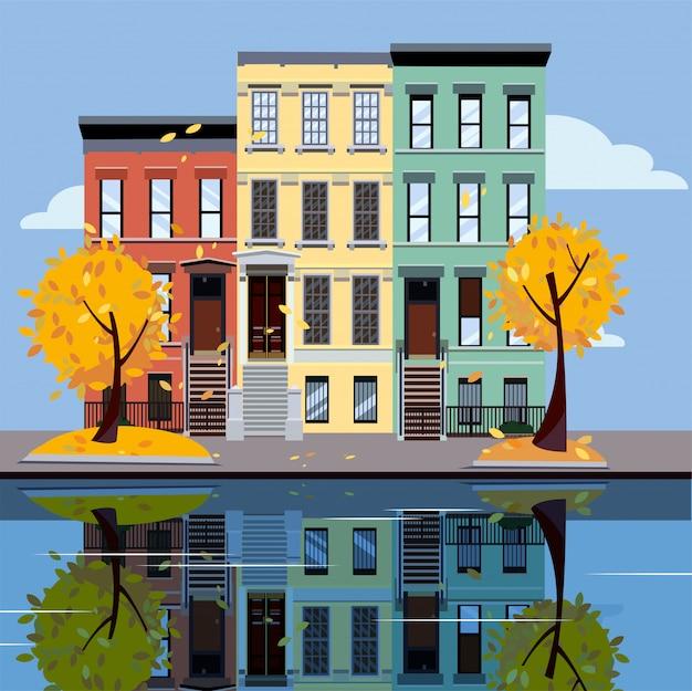 Жилые дома на озере. яркие фасады зданий. осенний город. улица городской пейзаж. Premium векторы