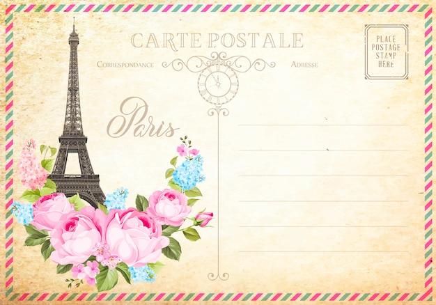 Старая пустая открытка с почтовыми марками и эйфелева башня с весенними цветами на вершине. Premium векторы